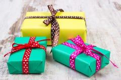 Cadeaux colorés enveloppés pour Noël ou toute autre célébration sur la vieille planche blanche Images libres de droits
