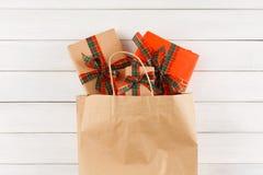 Cadeaux créatifs de Noël dans le sac de papier sur le fond en bois blanc de table Photographie stock