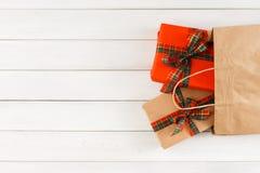 Cadeaux créatifs de Noël dans le sac de papier sur le fond en bois blanc de table Photographie stock libre de droits