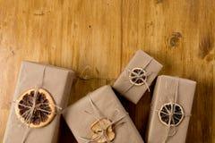 Cadeaux décorés de l'agrume sec sur la vue supérieure de fond en bois image libre de droits