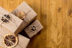 Cadeaux décorés de l'agrume sec sur la vue supérieure de fond en bois photographie stock
