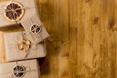 Cadeaux décorés de l'agrume sec sur la vue supérieure de fond en bois photos libres de droits