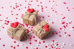 Cadeaux d'emballage au papier beige de métier de vintage et aux coeurs doux rouges de sucrerie de sucre Sur le fond rose avec arr Photo stock