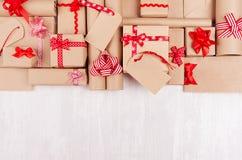 Cadeaux de célébration de Noël avec les rubans rouges et arcs, label vide sur le fond en bois blanc, l'espace de copie, vue supér image stock