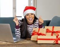 Cadeaux de Noël de achat de femme attirante heureuse en ligne utilisant la carte de crédit semblant excitée photos stock