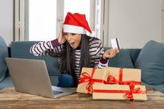 Cadeaux de Noël de achat de femme attirante heureuse en ligne utilisant la carte de crédit semblant excitée photographie stock