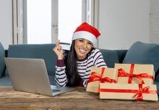 Cadeaux de Noël de achat de femme attirante heureuse en ligne utilisant la carte de crédit semblant excitée photo libre de droits