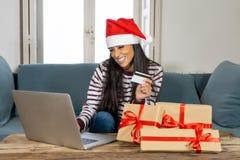 Cadeaux de Noël de achat de femme attirante heureuse en ligne utilisant la carte de crédit semblant excitée image libre de droits