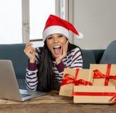 Cadeaux de Noël de achat de femme attirante heureuse en ligne utilisant la carte de crédit semblant excitée images stock