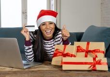 Cadeaux de Noël de achat de femme attirante heureuse en ligne utilisant la carte de crédit semblant excitée photos libres de droits