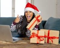Cadeaux de Noël de achat de femme attirante heureuse regard en ligne excité image libre de droits