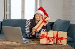 Cadeaux de Noël de achat de femme attirante heureuse regard en ligne excité avec des cadeaux photos libres de droits
