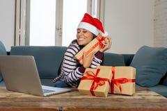 Cadeaux de Noël de achat de femme attirante heureuse regard en ligne excité avec des cadeaux photo stock