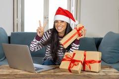 Cadeaux de Noël de achat de femme attirante heureuse regard en ligne excité avec des cadeaux photographie stock