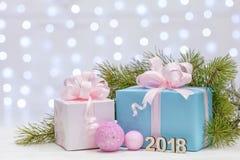 Cadeaux de Noël avec de grands arcs enveloppés en papier rose et nu, mensonge sur une surface en bois avec les branches impeccabl Image libre de droits