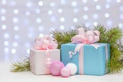 Cadeaux de Noël avec de grands arcs enveloppés en papier rose et nu, mensonge sur une surface en bois avec les branches impeccabl Image stock
