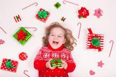Cadeaux de Noël d'ouverture de petite fille Photos stock