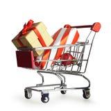 Cadeaux de Noël dans le caddie d'isolement sur le blanc photographie stock