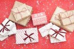Cadeaux de Noël enveloppés dans le papier d'ornement et le ruban décoratif de corde rouge sur la surface rouge Passe-temps créati image stock
