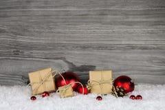 Cadeaux de Noël enveloppés en papier décoré des boules rouges dessus Photographie stock libre de droits