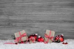 Cadeaux de Noël enveloppés en papier décoré des boules rouges dessus Image stock