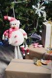 Cadeaux de Noël et un bonhomme de neige de jouet sous l'arbre Photo stock