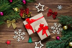 Cadeaux de Noël mignons sur la table en bois entourée avec la tresse de nouvelles années telle que des cloches, flocons de neige, Photos libres de droits