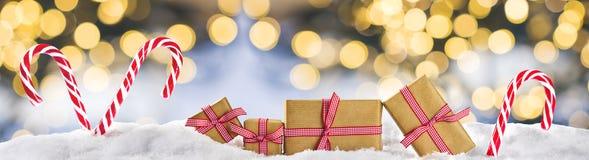 Cadeaux de Noël sur la bannière de neige, bokeh léger Photographie stock libre de droits