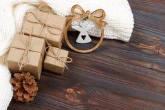 Cadeaux enveloppés de Noël avec la statuette blanche d'ange sur la table en bois rustique foncée avec des cônes de pin Avec l'esp Photographie stock libre de droits