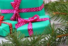 Cadeaux enveloppés pour Noël et branches impeccables sur la vieille planche Photographie stock libre de droits