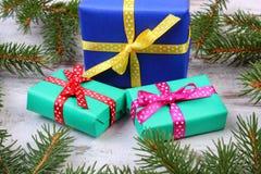 Cadeaux enveloppés pour Noël et branches impeccables sur la vieille planche Image libre de droits