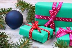 Cadeaux enveloppés pour Noël et branches impeccables sur la vieille planche Images libres de droits