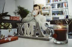 Cadeaux et bougie de décorations de Noël à la maison où un jeune homme s'assied sur le divan buvant seule la boisson chaude photographie stock libre de droits