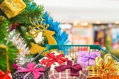 Cadeaux et présents de Noël dans le chariot de chariot à achats avec le fond d'arbre de Noël Photos stock