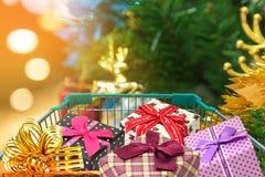 Cadeaux et présents de Noël dans le chariot de chariot à achats avec le fond de décorations d'arbre de Noël Photos libres de droits