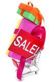 Cadeaux et une enseigne avec la vente de mot dans un caddie Image libre de droits