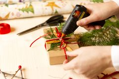 Cadeaux faits maison de femmes avec l'arme à feu de colle pour Noël Photographie stock