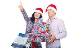 Cadeaux heureux de Noël de fixation de couples et pointage vers le haut Photographie stock