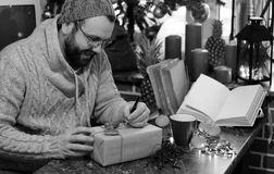 Cadeaux monochromes de Noël d'écriture d'homme de barbe sur une table Photos stock