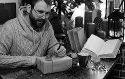 Cadeaux monochromes de Noël d'écriture d'homme de barbe sur une table Photographie stock