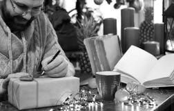 Cadeaux monochromes de Noël d'écriture d'homme de barbe sur une table Photographie stock libre de droits