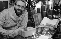 Cadeaux monochromes de Noël d'écriture d'homme de barbe sur une table Photo stock