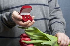 Cadeaux pour aimé Les hommes tient un bouquet des tulipes rouges dans sa main Dans l'autre main, une boîte ouverte de velours de  Images stock