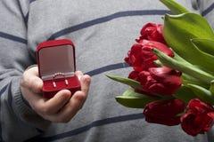 Cadeaux pour aimé Les hommes tient un bouquet des tulipes rouges dans sa main Dans l'autre main, une boîte ouverte de velours de  Photographie stock libre de droits