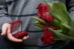Cadeaux pour aimé Les hommes tient un bouquet des tulipes rouges dans sa main Dans l'autre main, une boîte ouverte de velours de  Photo libre de droits