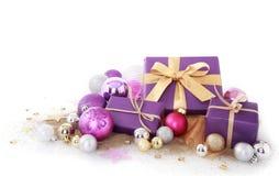 Cadeaux pourpres avec les boules assorties de Noël de taille Photo stock