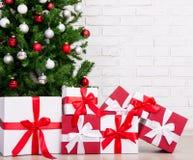 Cadeaux sous l'arbre de Noël décoré avec les boules colorées Photo libre de droits