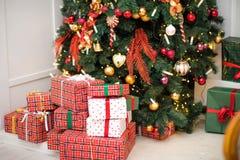 Cadeaux sous les lumières d'arbre de Noël images stock