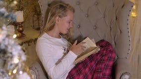 Cadeira acolhedor e uma menina bonita, lendo o livro velho, os conceitos da casa e o conforto Primeiro plano da árvore de Christm filme