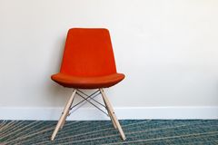 Cadeira alaranjada na frente da parede leve Imagem de Stock Royalty Free